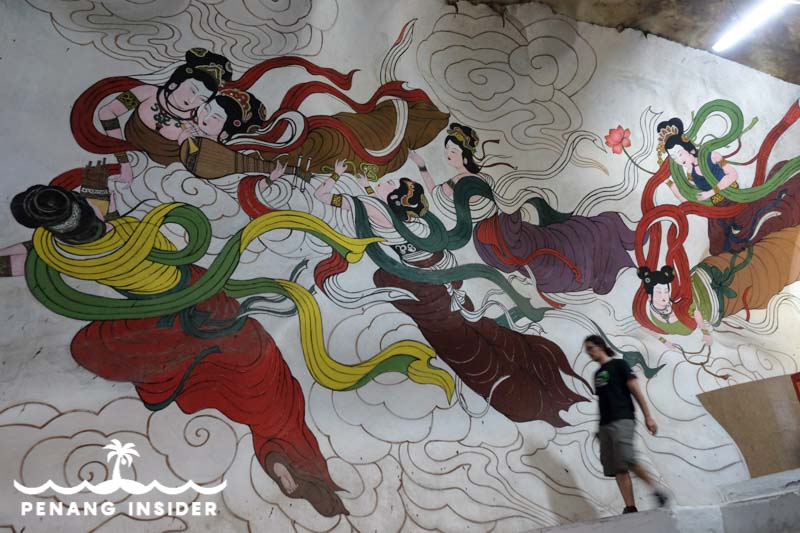 Colorful mural paintings depicting Buddhist deities and Chinese mythology adorn the inner walls of the Perak Tong Cave Temple in Ipoh