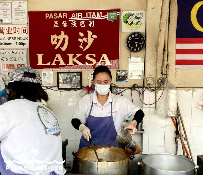 Chinese woman in face-mask Dishing up the famous Penang Laksa Air Itam