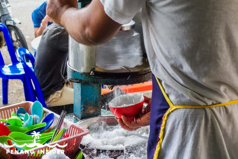 The shaving of the ice using traditional hand-operated machines at Ansari Cendol in Taiping