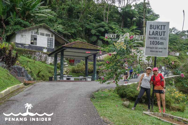 People standing in front of Bukit Larut station sign on Maxwell Hill Taiping