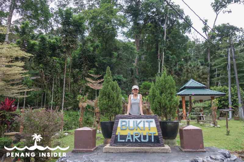 Kit Yeng Chan poses with Bukit larut sign at the bottom of Maxwell Hill in Taiping
